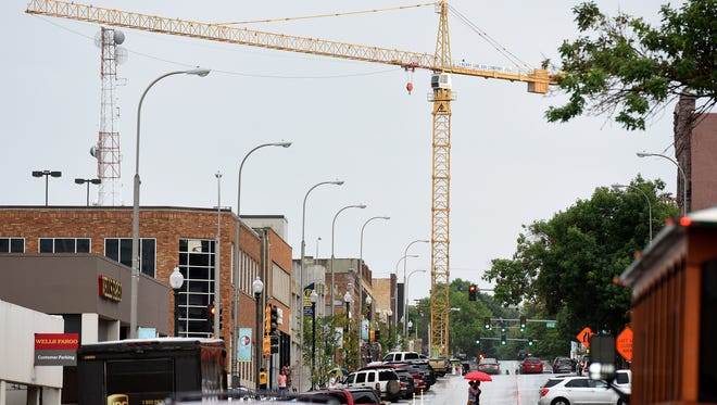 A giant yellow crane stands at 171 feet 5 inches, with a 230-foot working boom at its peak at the Washington Square project site along Main Avenue in downtown Sioux Falls.