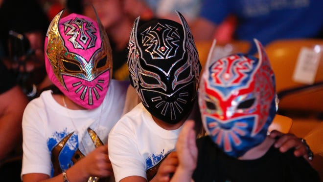 Fans wear Sin Cara masks at the WWE live event at the Don Haskins Center last month.