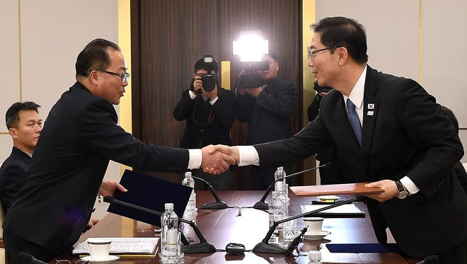 In this handout image provided by the South Korean Unification Ministry, South Korean Vice Unification Minister Chun Hae-Sung, shakes hands with the head of North Korean delegation Jon Jong-Su after their meeting on Jan. 17, 2018 in Panmunjom, South Korea. South and North Korea agreed to field a joint women's ice hockey team for the PyeongChang Winter Olympics.