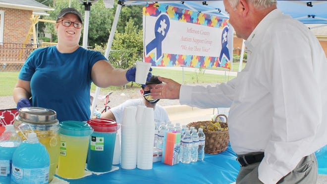 A volunteer hands a cup of lemonade to Jerry Taylor (at right). Taylor stopped by the lemonade stand Saturday. Proceeds went to Jefferson County Autism Support Group.
