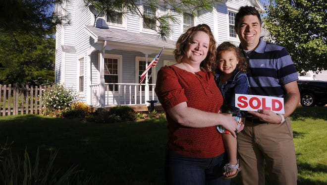 MacKenzie and Adam Feldpausch with daughter Tess, 3, outside the home they are buying in DeWitt Township.  Picture taken Thursday    8/28/2014.