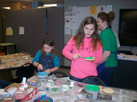 Rozellville Rockets 4-H Club members decorate cookies to sell, along with ice cream, Dec. 1 and 2 at Hub City Ice Cream Co. in Marshfield.