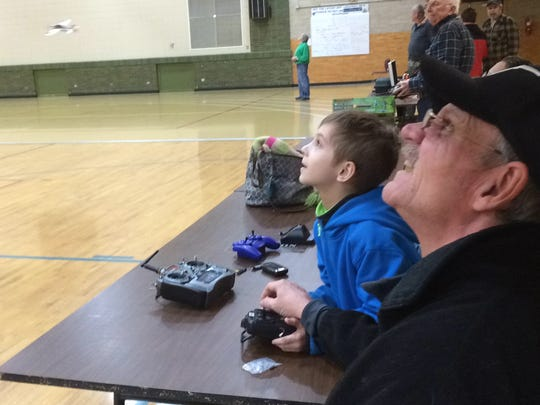 """Geoff Stoner of Wisconsin Rapids keep an eye in the """"sky"""" as he and others watch radio-controlled-aircraft fly inside the East Junior High School gym during a recent Friday night River Valley Flyers flight night. A member of the club flies a model at the far right."""