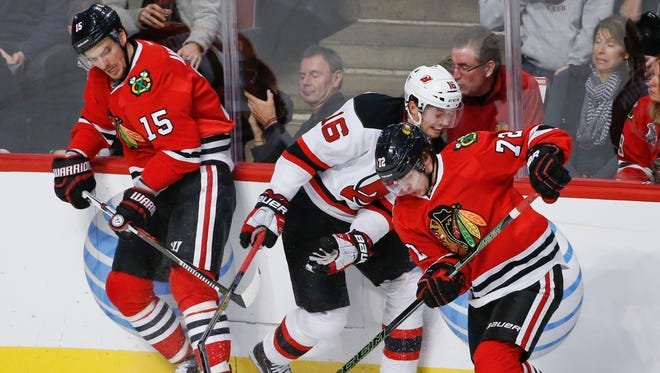 Chicago Blackhawks center Artem Anisimov (15) and left wing Artemi Panarin (72) battle for the puck with New Jersey Devils center Jacob Josefson (16) during the second period at United Center.