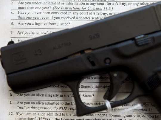 A handgun sits on top of a form used for firearms transactions. Under federal law, there are many reasons why someone could be banned from possessing a gun. The list includes a previous felony conviction or misdemeanor of domestic violence conviction.