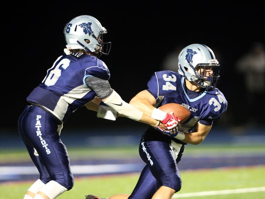 John Jay quarterback Richie Eletto (16) hands off to
