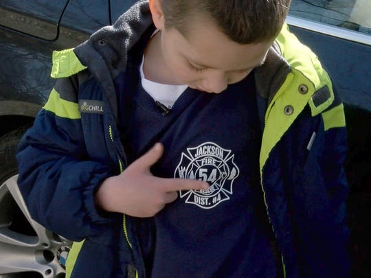 Jace Sorchinski shows off his Jackson Township fire company shirt outside his family's home in Jackson Sunday, January 21, 2018.   His mother Nicole had a seizure driving the two of them to McDonald's. She pulled over in time, but may have stopped breathing. Jace called 911 and kept talking to her through the seizure, possible saving her life.