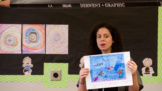 Sharon Elementary School art teacher Jessica Moyes displays a student's fish aquarium project as an example to her class Wednesday morning. The finished projects will be framed, displayed and possibly sold at their December show.
