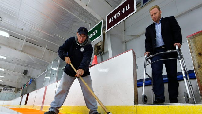 As injured hockey player Thomas Smith looks on, rink worker Carl Ellis paints a 40-inch-wide orange Look-Up Line on the ice at Pingree School in Massachusetts.