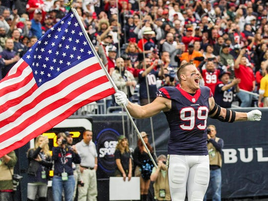 Houston Texans defensive end J.J. Watt (99) runs onto the field with a flag before a game against the New York Jets at NRG Stadium.