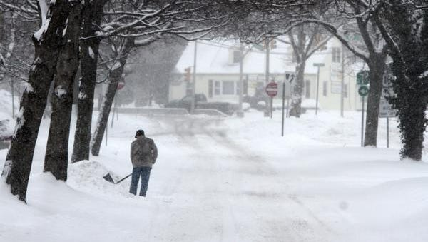 A resident in East Brunswick, N.J., shovels snow from his driveway Jan. 27, 2015. A couple of teens in Bound Brook, N.J., tried to earn some money shoveling but were stopped by police because of a local ordinance violation.
