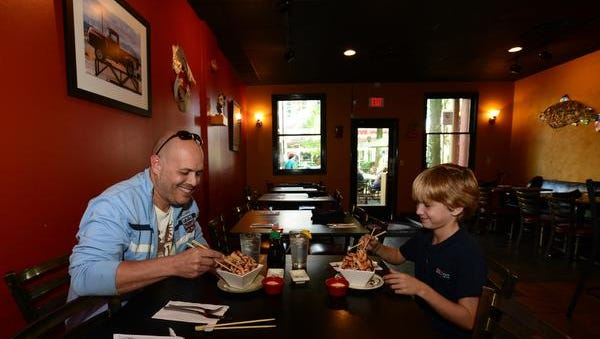 Bruce Plourde and his son London, 10, eat squid salad at Takosushi on Tuesday, October 7, 2014.