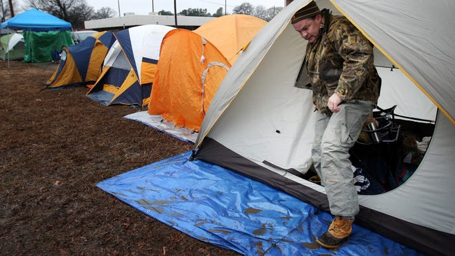 "January 21, 2016 - Andy Rambo exits the warmth of this semi-heated tent outside the Shelby County Schools board of education on Avery where he is among 84 parents camped out to increase the chances of securing a place for their children at an optional school. The parents, most of which were trying to get children into the Maxine Smith STEAM Academy, were hopeful the early State of Emergency declaration for Tennessee might lead to getting placeholder numbers to return Monday morning so they don't have to sleep in the cold with an expected winter storm rolling across the Mid-South. ""Worst case senario you can get in your car to escape the cold."" Rambo said. (Mike Brown/The Commercial Appeal)"