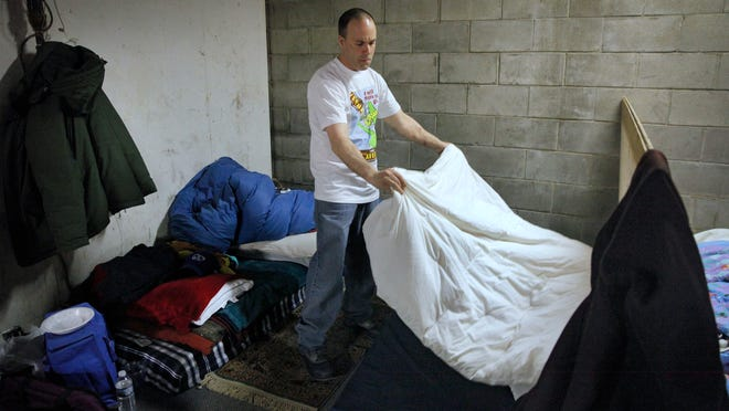 Joey Daddazio makes his bed in the space he shares with his brother at the indoor Sanctuary Village for the homeless in a Canal Street building owned by Buckingham Properties.