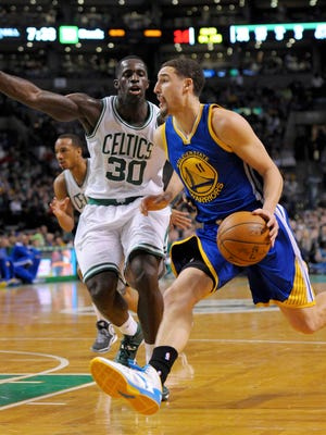 Golden State Warriors guard Klay Thompson (11) drives to the basket while Boston Celtics center Brandon Bass (30) defends during the second half at TD Garden.