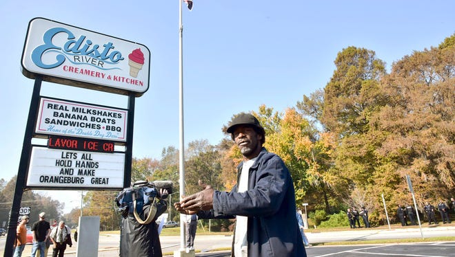 FILE - in this Nov. 16, 2016 file photo, Andre Washington stands outside Edisto River Creamery and Kitchen in Columbia, S.C. Washington was one of several dozen people who came to the Edisto River Creamery  with hopes of seeing the Confederate Flag removed.  Enraged that a Confederate flag continues to fly outside his ice cream shop and confuse customers, Edisto River Creamery owner Tommy Daras is now warning the flags' caretakers that he is going to dig up a nearby marker honoring rebel soldiers. But the owners of the monument said they will have him arrested if he follows through on his threat, arguing that they own the tiny piece of land on which the monument and flag are located. (Larry Hardy/Times & Democrat via AP)