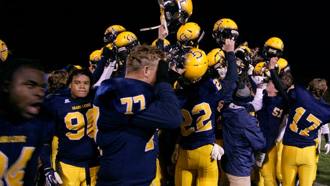 Grand Ledge players celebrate after their 31-21 win over East Lansing.