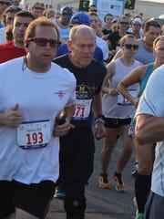 Acie Stanfill (center) begins the Battle Creek Half Marathon on Saturday, June 30, 2018.
