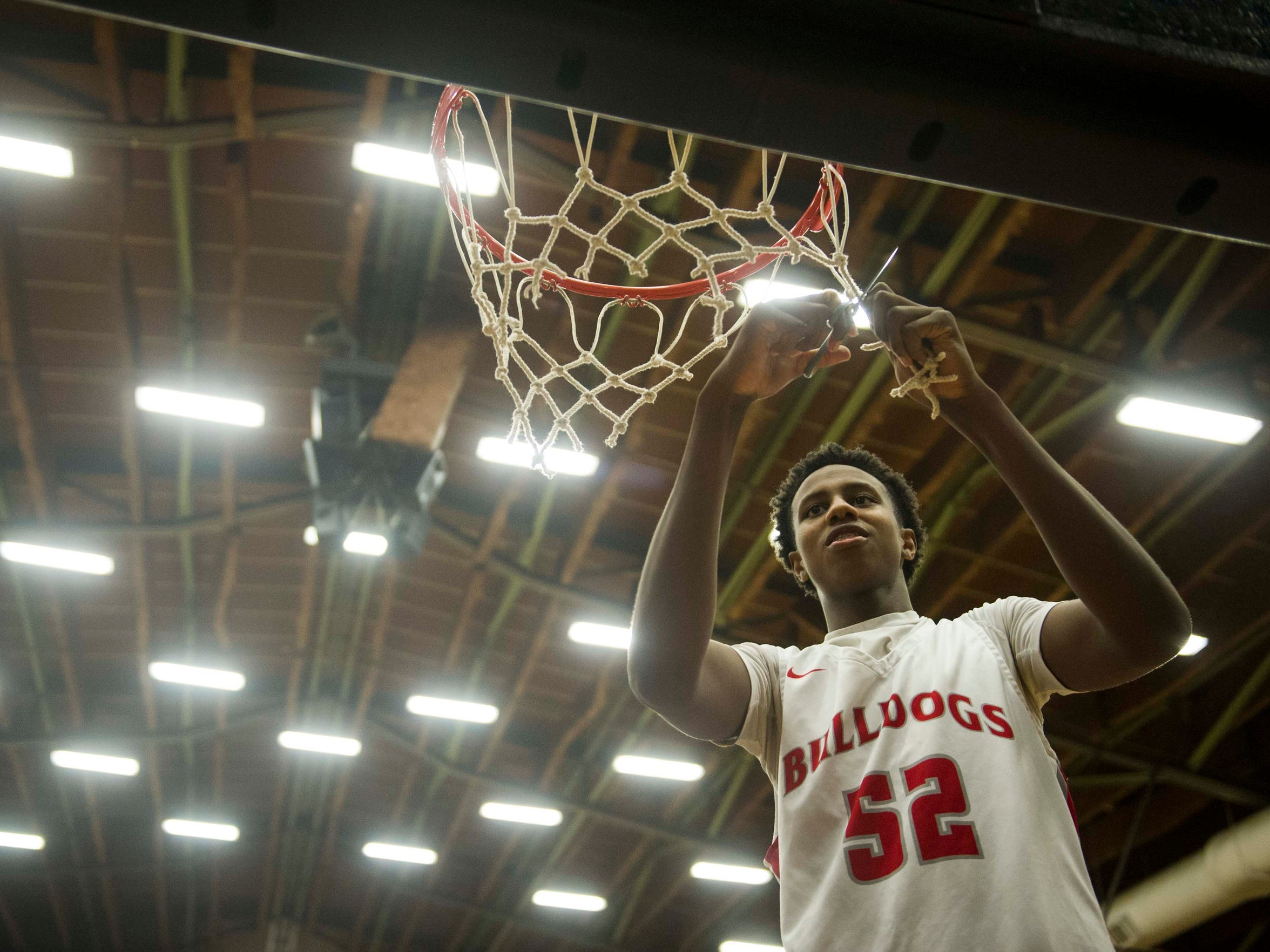 Bosse's Kiyron Powell (52) cuts down part of the net after defeating Memorial in the Class 3A Boonville Sectional final at Boonville High School on Saturday, March 3, 2018. Bosse defeated Memorial 67-62.