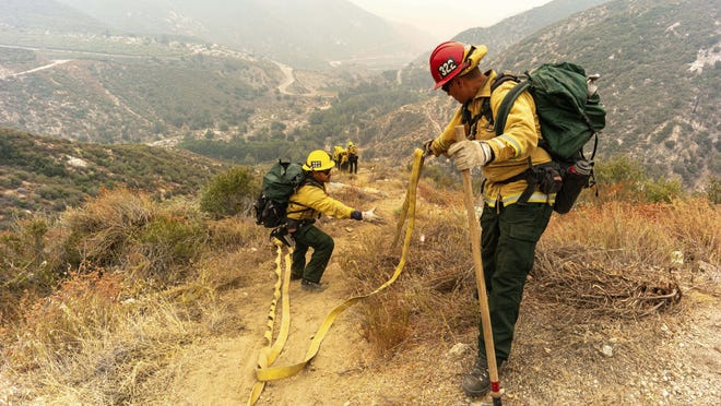 Members of the Mormon Hot Shots from Arizona lay hose line down rugged terrain off Highway 39 near Crystal Lake in front of the Bobcat Fire, in California, which has burned more than 23,000 acres, Thursday, Sept. 10, 2020.
