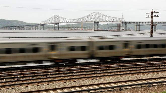A Metro-North train streaks along the Hudson River just south of the Tappan Zee Bridge earlier this year.