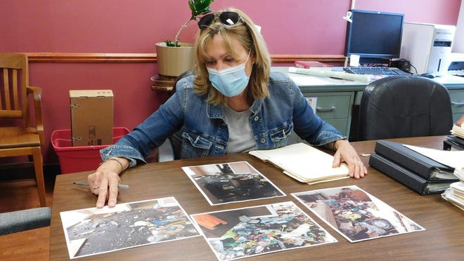 Herkimer Code Officer Tina Cirelli shows copies of photographs taken in some local apartments where codes officers have found squalid conditions.