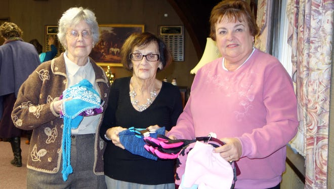 (From left) Noreen Thorwarth, Janice McCann and Norene Ritter, all members of the Woman's Club of Vineland, with some of the winter accessories members collected for St. Vincent de Paul Society.