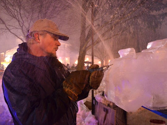 ice carver Ted Wakar works in the rain during a previous ice festival.