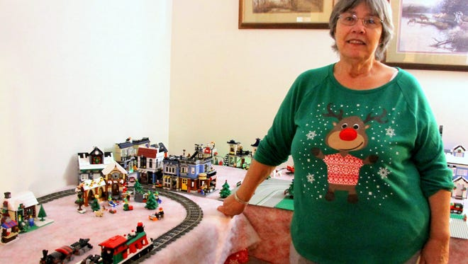 Debra Packer stands with her LEGO Christmas village in her home.