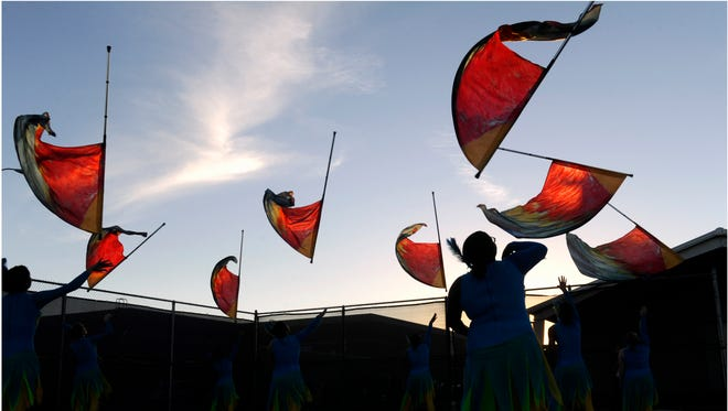 Cooper High School senior Octavia McGee is silhouetted as she practices with the Awesome Cooper Band color guard prior to performing Oct. 23 at the UIL Region 6 East Zone Marching Contest. Fifteen schools competed at Wylie High School's Bulldog Stadium, where Cooper earned a 1 rating to advance to the area contest.