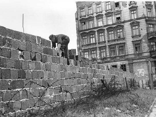 An East Berlin policeman puts bricks in place as the