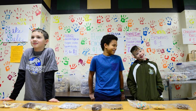 Wilson Junior High School students Allen Lagerstrom, left, Marcos Valenzuela and Andrew Haney help at the bake sale table before school begins on Dec. 3. The items were made by  students to raise money for Jacklynn Gienke.