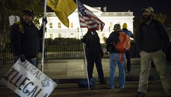 A member of the Secret Service's uniformed division talks with anti-amnesty activists as they gather on Pennsylvania Avenue before the White House November 20, 2014 in Washington, DC.
