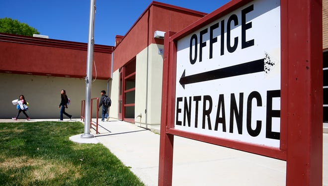 Secretary Gloria Shirley said the current interior doors of the main entrance to Apache Elementary School, seen here, will be locked during school hours and visitors will have to walk past staff members in the office and then be buzzed in through a new security door to gain access to the building. Students can be seen heading home from the school on Thursday.