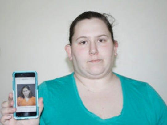 Dorothy Varallo-Speckeen, 26, holds up her mug shot