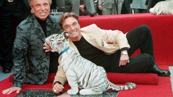 Illusionists Siegfried Fischbacher, left and Roy Uwe Ludwig Horn pose for photographers with a white tiger cub after they unveiled their star on the Hollywood Walk of Fame in 1994. German news agency dpa is reporting that Fischbacher, the surviving member of duo Siegfried & Roy, has died in Las Vegas at age 81.