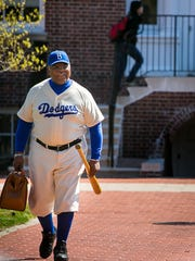 Wearing a Jackie Robinson baseball outfit, UD professor Ron Whittington, walks near Memorial Hall on the University of Delaware campus.