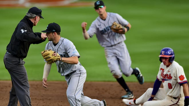 Coastal Carolina's Cory Wood, left, and Scott McKeon, center, react after tagging Clemson's Logan Davidson, right, out at second base during a game March 13, 2019 in Clemson, S.C. Coastal Carolina already had a small athletic budget, and that was before a 15% spending cut was ordered because of projected declines in state funding and student fees stemming from the coronavirus pandemic.