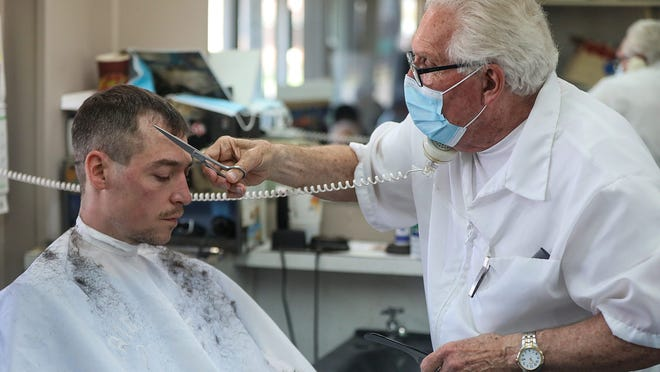 Karl Manke, a barber in Owosso, cuts Brandon Lamrouex's hair while answering nonstop phone calls at his barbershop on May 6, defying Michigan Gov. Whitmer's order for non-essential businesses to be closed. The Michigan Supreme Court on Friday overturned orders that directed a barber to close his shop during the coronavirus pandemic.