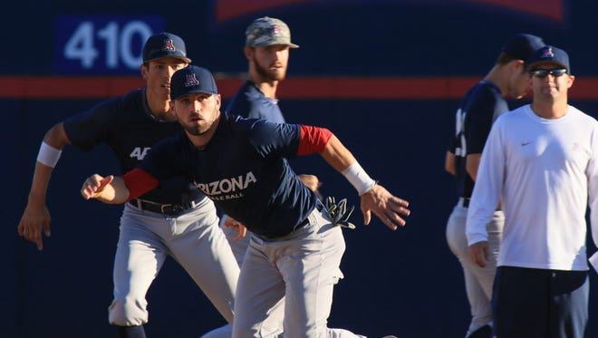 Arizona's Cody Ramer, foreground left, and Ryan Aguilar, left, practice running drills on Monday.