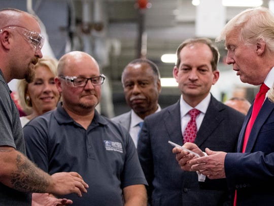 President Donald Trump, accompanied by Education Secretary Betsy DeVos, second from left, and Labor Secretary Alexander Acosta, second from right, tours Waukesha County Technical College in Pewaukee, Wisconson, in June 2017.