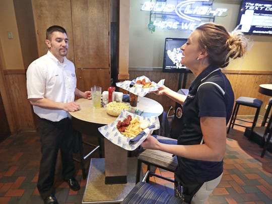 Bartender Amber Buth delivers a lunch order to Jack Terrien on Monday at The Bar on Lime Kiln Road. Its menu has come a long ways from the early days of frozen pizzas and free peanuts on Wednesdays.