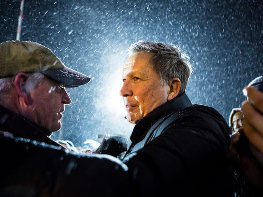 John Kasich walks back to his bus after thanking his