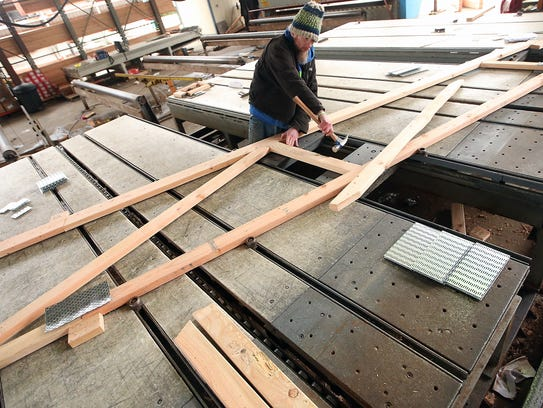 Tim Shattun assembles a truss at Kingston Lumber. Workers who survived layoffs after the recession began endured cuts to their pay and benefits.