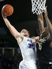 MTSU's Reggie Upshaw Jr. (30) is fouled by Vanderbilt's Clevon Brown (15) as Upshaw goes for a shot during the game, on Thursday, Dec. 8, 2016, at MTSU.
