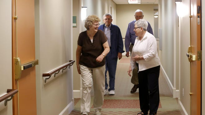 Erma Joslin (left) laughs as she and Gloria Moon lead their husbands Paul Joslin (back left) and Donald Moon down the hall to dinner Thursday, July 30, 2015, at the Deerfield senior living community in Urbandale.