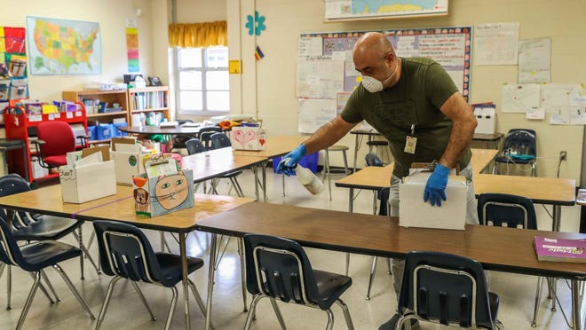 Galindo Elementary School custodian Ivan Tovar performs disinfection work in one of the school's classrooms. On Wednesday, teachers in the Austin school district called on leaders to move classes online for at least the first half of the fall semester.