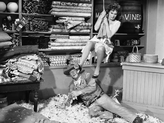 "Maureen O'Hara, clad in pantaloons, swings over John Wayne in scene from ""McLintock,"" a new movie being filmed in Hollywood, Los Angeles on Jan. 15, 1963. Wayne, who has slipped in a mess of molasses and chicken feathers, plays the part of a rugged cattle baron, banker and town power trying to keep his wife, O'Hara, from divorcing him. (AP Photo/Don Brinn)"