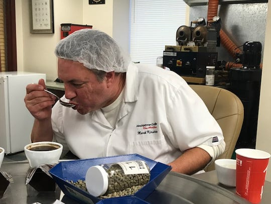 Mark Kirstein tastes coffee during the cupping process