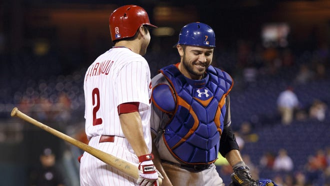 The Phillies' Chase d'Arnaud (left) has a word with his brother, New York Mets catcher Travis d'Arnaud, before his at-bat during the seventh inning Tuesday in Philadelphia.